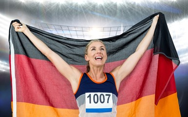 Composite image of athlete posing with german flag after victory