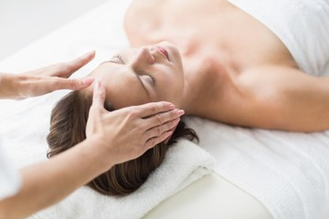Cropped hands of therapist performing reiki on woman