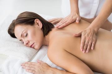 Naked woman receiving massage from masseur