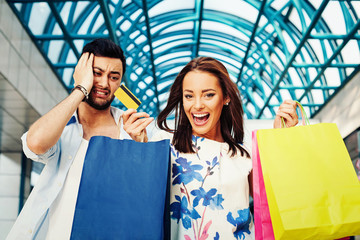 Worried man and happy woman with credit card and shopping bags