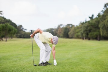 Mature man holding golf club while bending