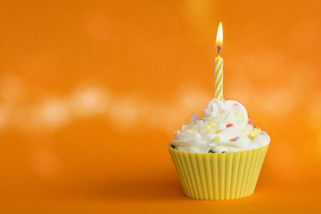 yellow cupcake with burning candle and orange background