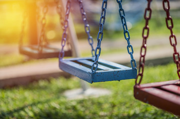Empty chain swing in playground. vintage filter