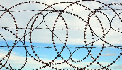 Patterns in a tangled barbed wire fence with sky background