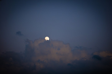 full moon hiding behind the clouds at night