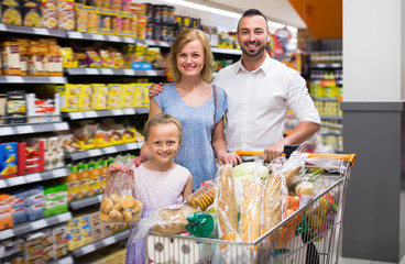 Happy parents with girl shopping in hypermarket