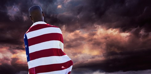 Composite image of rear view of man wearing american flag