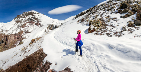 woman hiking on a snowy trail in the Caucasus mountains on the background of unusual lenticular cloud