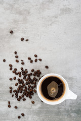 Coffee and coffee beans on concrete background