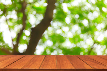 Wood table top on blur green tree background. For display products