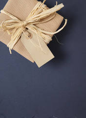 Gift border - Present wrapped in brown parcel paper with blank gift tag and raffia bow arranged on a rustic slate background to form a page border