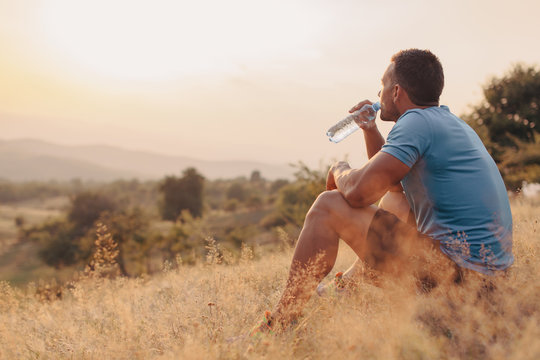 Athletic man in his 30s resting and drinking water from a bottle while sitting down outdoor