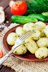 lunch or dinner , boiled potatoes with dill and fresh vegetables , cucumbers, tomatoes and spices on wooden background
