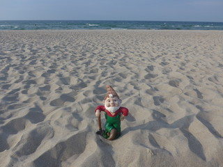 Garden gnome with shovel on vacation at sea