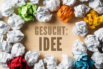 """zerknüllte Papierkugeln als Symbol für verworfene Ideen mit dem Slogan """"Gesucht: Idee"""""""