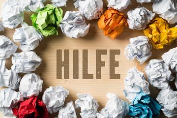 zerknüllte Papierkugeln als Symbol für Einfallslosigkeit und dem Wort Hilfe