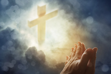 Praying hands and cross in heavenly sky