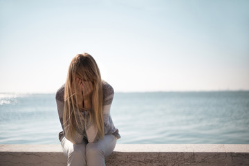 Sad woman sitting on stone wall with sea in the background, crying and covering her face.