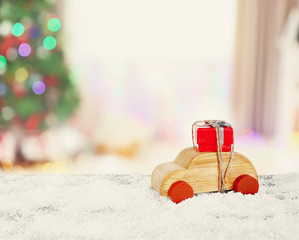 Wooden toy car carrying Christmas miniature gift on shiny lights background