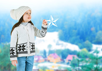 Little girl in a trendy knitted clothes on blurred landscape background