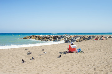 Relaxed man sitting in a beautiful mediterranean beach next to a few pigeons.