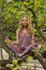 The girl meditates sitting on tree in the garden