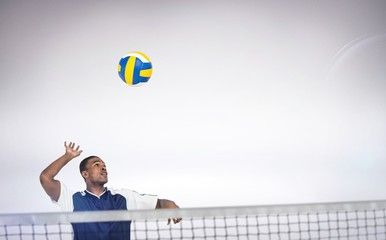 Composite image of sportsman posing while playing volleyball