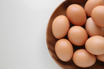 Eggs in wooden bowl on white table copy space background