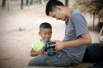 smart photographer  and smiling boy looking photos in camera at old home