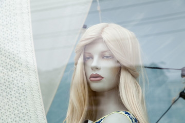 Cute realistic female mannequin face close-up in a shop window