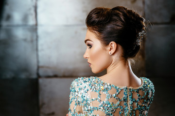 Beautiful brunette girl in an expensive turquoise dress with rhinestones. Metal background. Advertising Space.