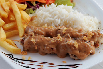 Chicken skewers on plate, garnished with sauce, rice, chips and vegetables