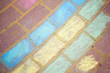 chalk drawing of rainbow and color chalks on asphalt