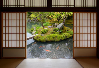 Sliding Japanese doors and fish pond with colorful orange carp swimming in the water