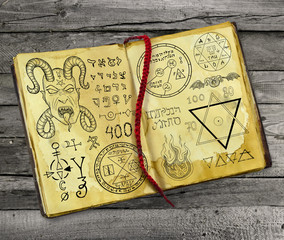 Old magic book with Devil and mystic symbols on wooden planks