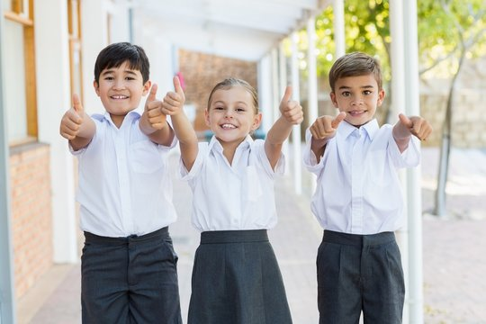 Smiling school kids showing thumbs up in corridor
