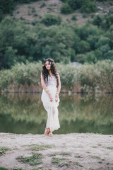 Beautiful young woman with long curly hair dressed in boho style dress posing near lake