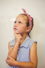 Thoughtful cute girl with hand on chin in classroom