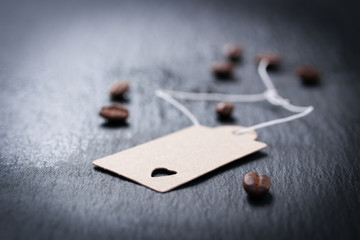 Paper tag with heart on a dark stone background with coffee on a background, closeup..