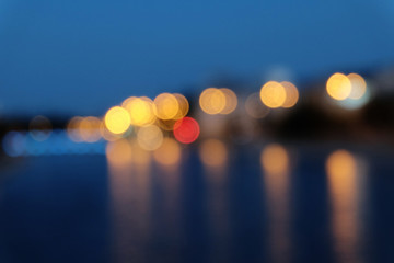 Wall Murals Blurred city lights with bokeh effect reflected on water surface.