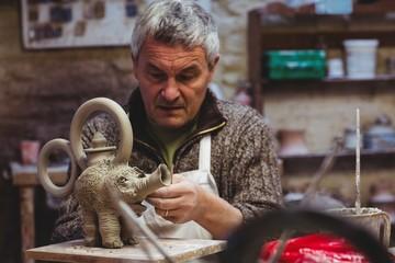 Mature artist preparing clay elephant