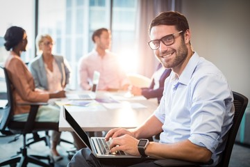 Man using laptop while coworker interacting in the background
