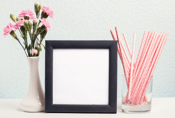 Pink flowers in a vase, paper straws and blank frame
