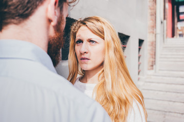 Couple of young beautiful redhead and blonde millennial woman and man staring each other, focus on her, serious - pensive, thoughtful, intense concept