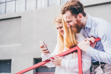 Couple of young beautiful redhead and blonde millennial woman and man looking the scren of a smart phone hand hold, smiling - happiness, technology, social network concept
