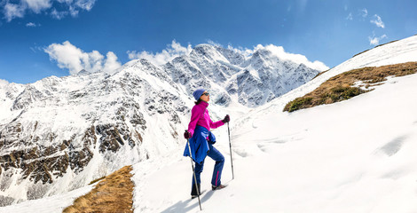 Sunny mountain slope covered with snow and woman climbing with trekking poles. Outdoor among mountain peaks concept