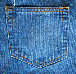Fashionable stack of jeans, trouser, clothes on a texure backgro