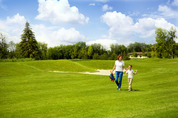 Mother teaching son to play golf