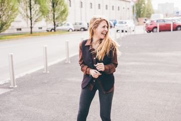 Knee figure of young beautiful caucasian blonde hair woman laughing outdoor in the city, overlooking - smiling, happiness, carefree concept