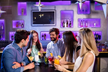 friends interacting with each other at bar counter